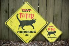 two identical signs one larger both yellow with cat crossing text and black cat silhouette with Tater in red graffiti